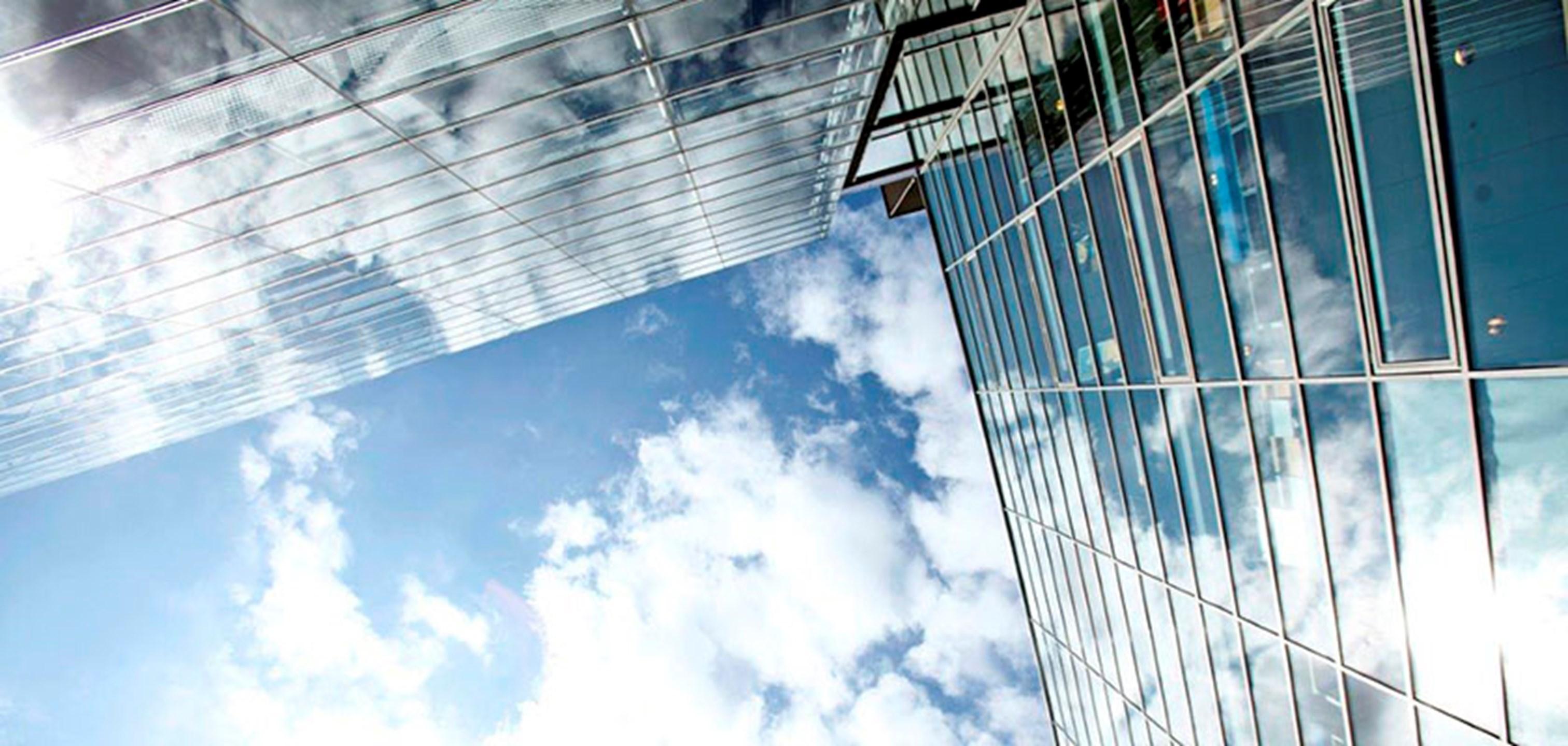Taivas ja rakennuksen lasi-ikkunat, kuvituskuva.